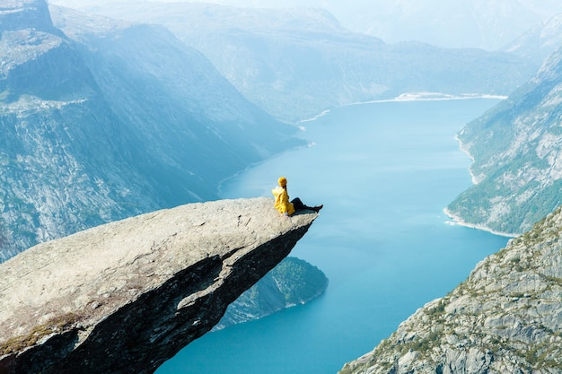 Uma garota com uma jaqueta amarela senta no trolltunga, na noruega