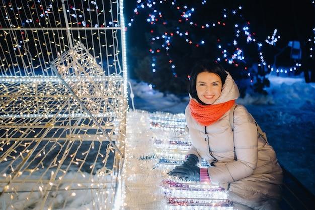 Uma garota com uma jaqueta cinza no inverno com as luzes da noite acesas na rua de natal.
