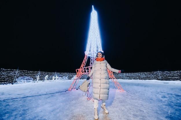 Uma garota com uma jaqueta cinza no inverno com as luzes da noite acesas na rua de natal