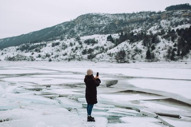Uma garota com uma jaqueta de inverno preta, tirando fotos da paisagem de inverno de um rio congelado com blocos de gelo.