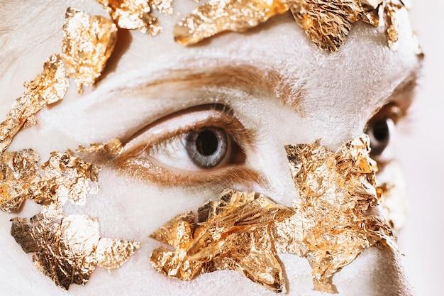 Uma garota com uma maquiagem incomum, com pele branca e olhos azuis. cílios longos. máscara de ouro. folha de ouro.