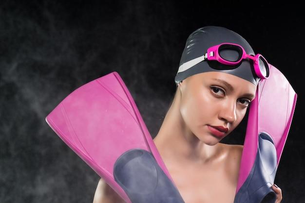 Uma garota com uma máscara de natação e um chapéu segurando nadadeiras