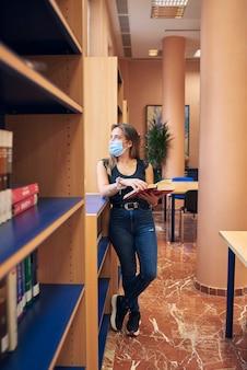 Uma garota com uma máscara está parada olhando pela janela da biblioteca