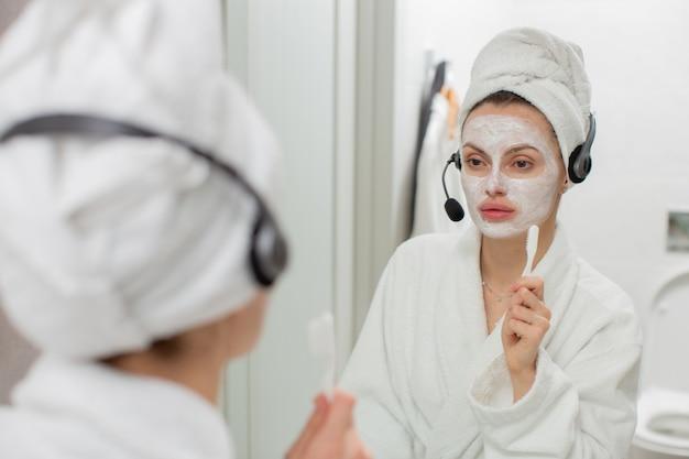 Uma garota com uma máscara facial de argila e fones de ouvido está no banheiro e se olha no espelho. foto de alta qualidade Foto Premium
