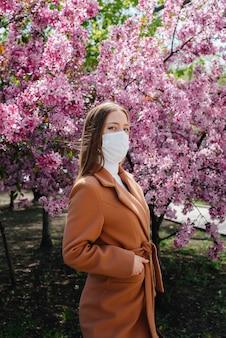 Uma garota com uma máscara fica perto de uma árvore de florescência.