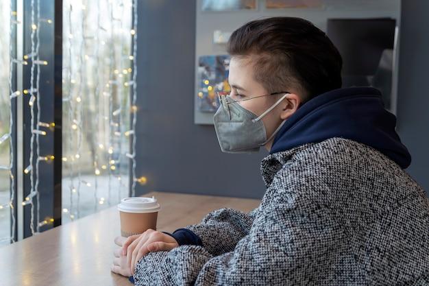 Uma garota com uma máscara médica está sentada em um café e olha tristemente pela janela
