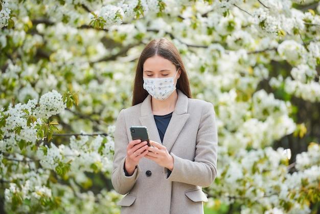 Uma garota com uma máscara médica para evitar a propagação do coronavírus lê as notícias em um smartphone. uma mulher com uma máscara facial contra o covid-19 mantém uma distância social no jardim entre árvores floridas.