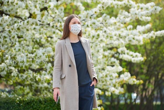 Uma garota com uma máscara médica para evitar a propagação do coronavírus segura um smartphone no parque. uma mulher com uma máscara facial contra o covid-19 mantém uma distância social no jardim entre árvores floridas.