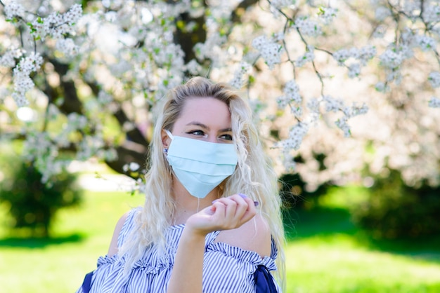 Uma garota com uma máscara médica protetora na primavera entre o jardim florido