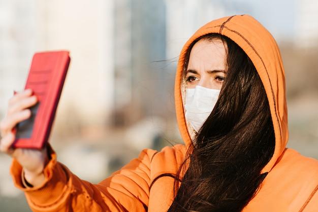 Uma garota com uma máscara médica se fotografa na rua durante a pandemia de coronavírus e covid - 19
