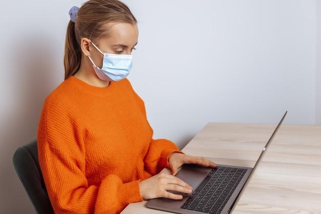 Uma garota com uma máscara médica trabalhando com um laptop