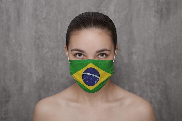 Uma garota com uma máscara no rosto com a bandeira do brasil