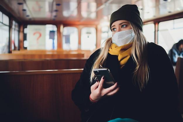 Uma garota com uma máscara protetora em um vagão do metrô com um telefone celular nas mãos