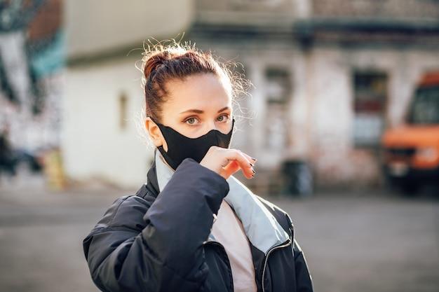 Uma garota com uma máscara protetora toca seu rosto