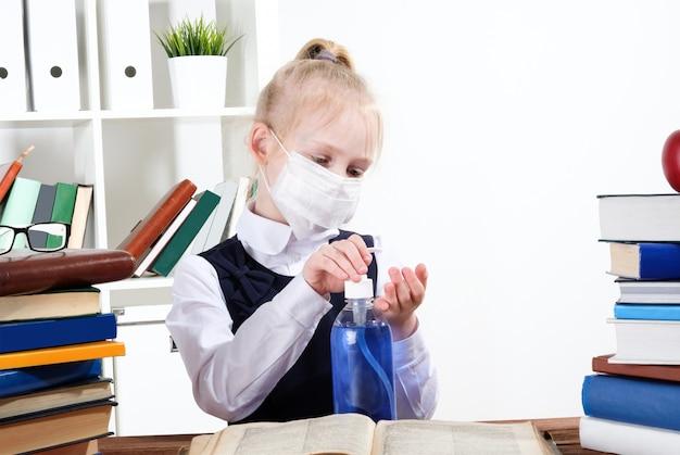 Uma garota com uma máscara protetora trata as mãos com um anti-séptico.