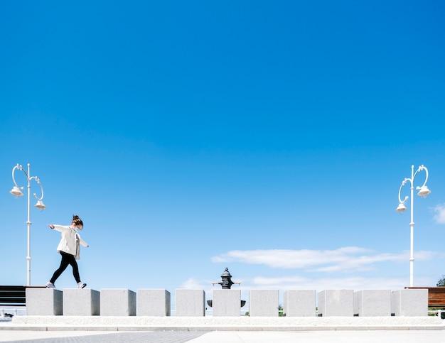 Uma garota com uma máscara se diverte pulando um muro em uma cidade a pé em um dia ensolarado