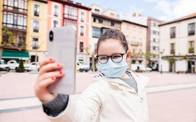 Uma garota com uma máscara tira uma selfie com o celular em uma praça da cidade