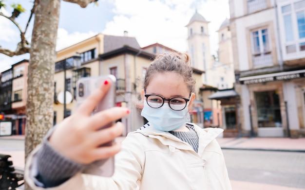 Uma garota com uma máscara tira uma selfie com o celular na cidade