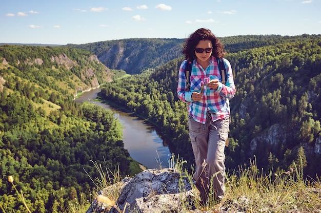 Uma garota com uma mochila fica em uma pedra em um vale e tem flores na mão.