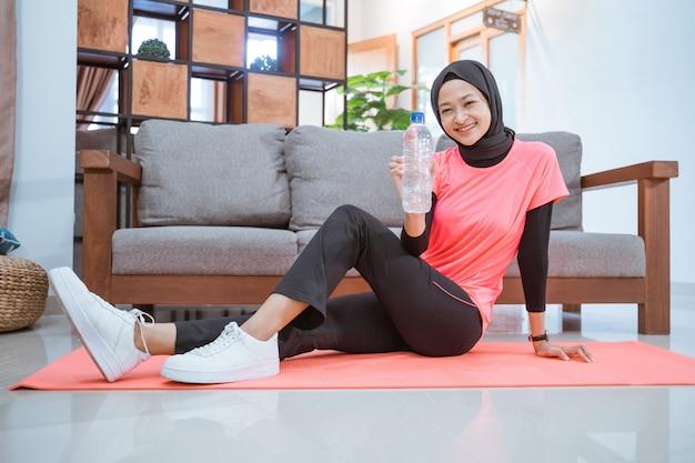 Uma garota com uma roupa de ginástica com lenço na cabeça sorri enquanto segura uma garrafa enquanto se senta no chão com uma esteira enquanto se exercita em casa
