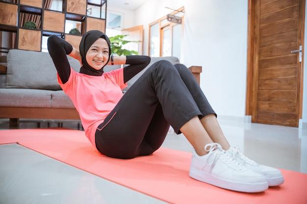 Uma garota com uma roupa de ginástica hijab sorri enquanto se senta em uma esteira no chão da casa