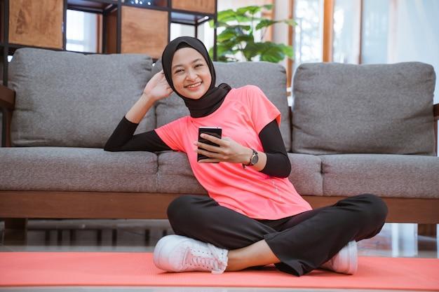 Uma garota com uma roupa de ginástica hijab sorridente segurando um celular enquanto está sentada relaxada no chão, encostada no sofá