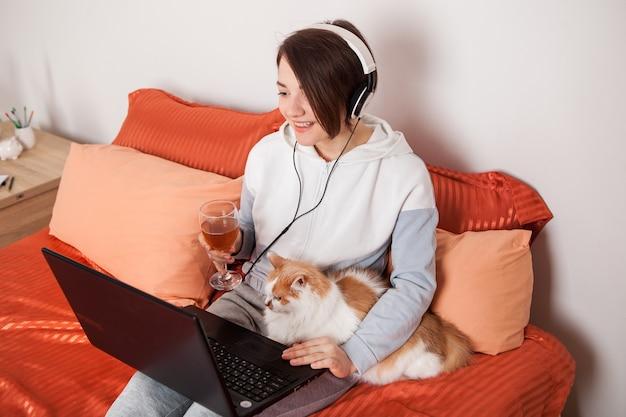 Uma garota com uma taça de vinho se comunica online com amigos e parentes.