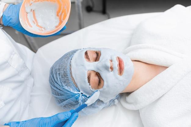 Uma garota com uma túnica branca recebe uma máscara de alginato no rosto.