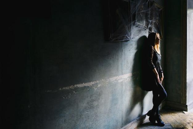 Uma garota com uma visão sonhadora se inclina para uma parede em um café