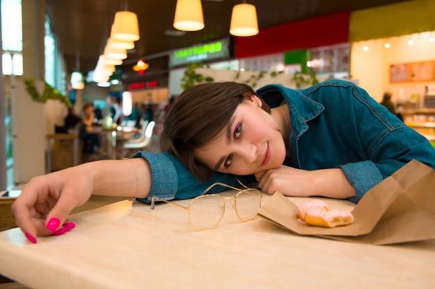 Uma garota come um donut em um shopping center, inclinando-se sobre uma mesa, penteado quadrado