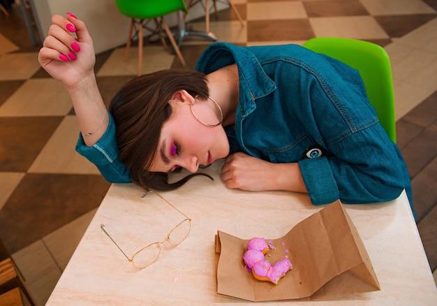 Uma garota come um donut em um shopping, encostada em uma mesa