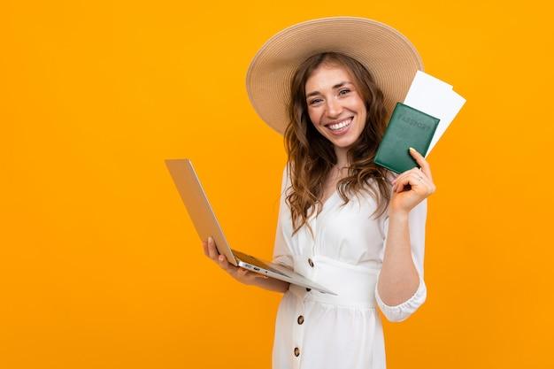 Uma garota compra passagens de avião pela internet, uma senhora elegante tem passaporte e passagens aéreas nas mãos de uma parede laranja