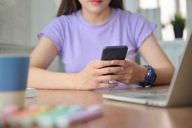 Uma garota conversando on-line com um amigo em um smartphone durante o intervalo do estudo.