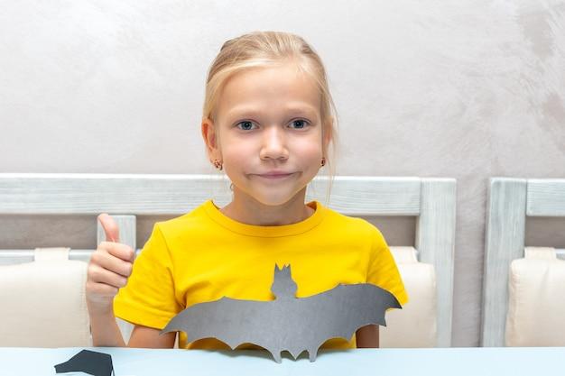 Uma garota corta um bastão de halloween com as próprias mãos de papel artesanal preto com uma tesoura em casa. a garota mostra um morcego