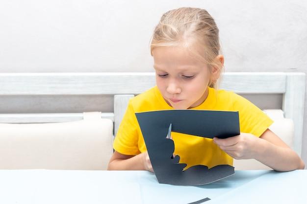 Uma garota corta um bastão de halloween com as próprias mãos de papel artesanal preto com uma tesoura em casa. conceito de férias de halloween em casa.