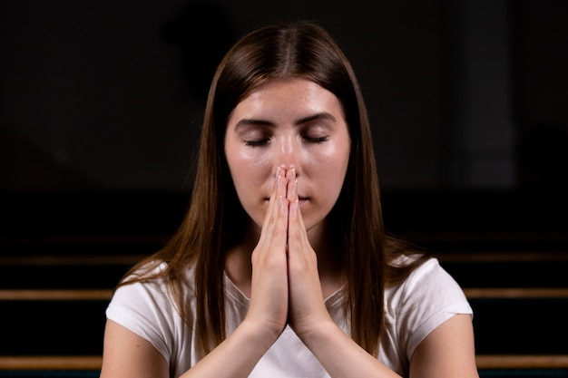 Uma garota cristã de camisa branca está sentada e orando com coração humilde na igreja