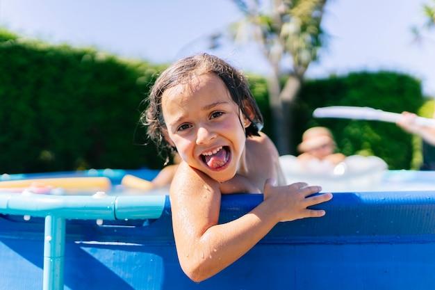 Uma garota curtindo na piscina de verão de sua casa