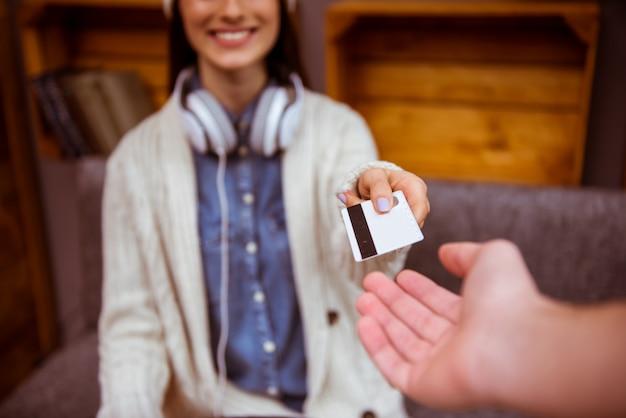Uma garota dá um cartão de crédito para pagar as contas em um café.