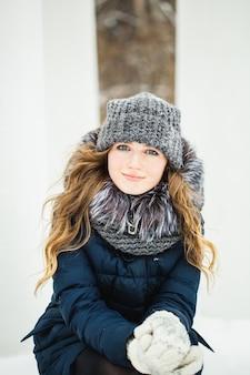 Uma garota de aparência européia caminha no parque ou floresta no inverno
