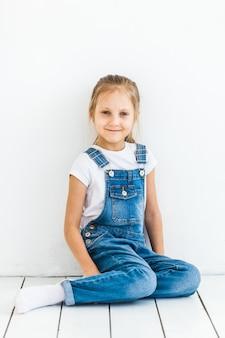 Uma garota de aparência européia, com cabelos longos claros, senta-se em um piso claro, vestida com uma camiseta e jeans, infância