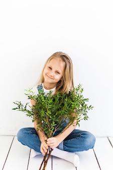 Uma garota de aparência européia, com cabelos longos claros, senta-se no chão e segura galhos de pistache, galhos verdes, plantas, interior