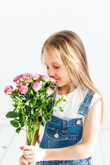 Uma garota de aparência europeia, com longos cabelos loiros, sorrindo, emoções, alegria, amizade, família, segurando rosas, flores delicadas, flores para sua mãe