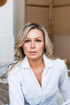 Uma garota de aparência européia está sentada em um colchão, vestindo uma blusa branca, jeans, moda, beleza, estilo