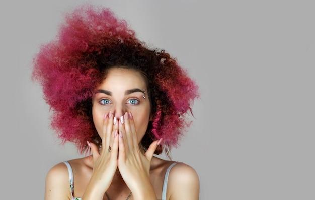 Uma garota de aparência européia, ucraniana, com olhos azuis e cabelos rosa, cobriu a boca com o retrato de mãos