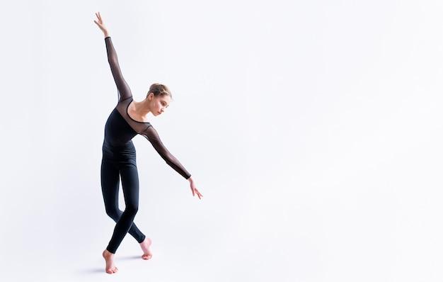 Uma garota de balé em um terno justo preto dança em um fundo branco com coreografia contemporânea moderna