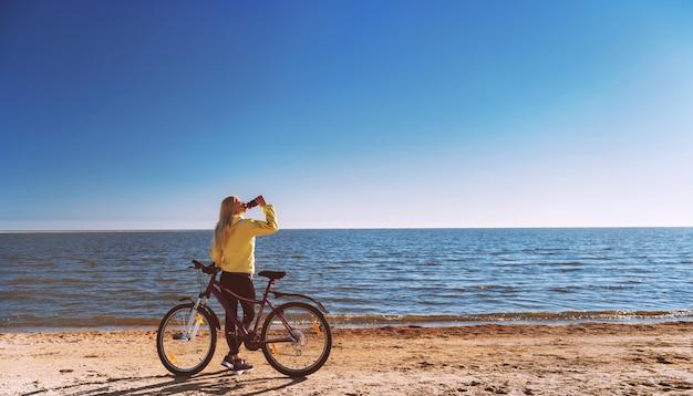 Uma garota de bicicleta à beira-mar