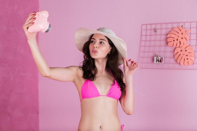 Uma garota de biquíni e chapéu de abas largas tira uma foto de selfie em uma câmera instantânea