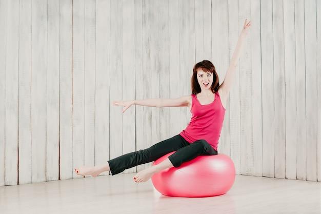 Uma garota de blusa rosa, sentada em uma fitball rosa em uma academia