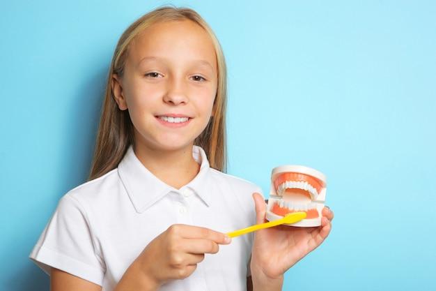 Uma garota de bom humor escova os dentes e segura um modelo de dentes