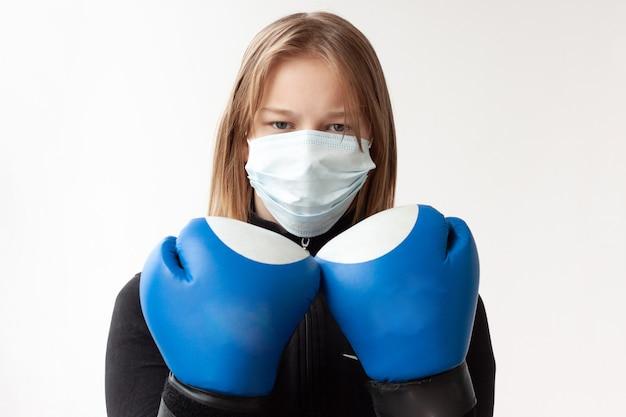 Uma garota de cabelo loiro com uma máscara médica e luvas de boxe azuis está em pose de boxeador, com as mãos perto do rosto.